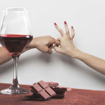 Red wine glass and chocolate with sex gesture